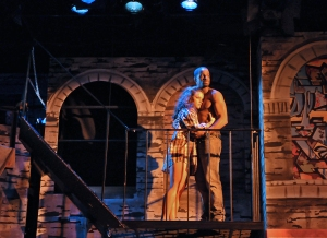 Santina Umbach and Jared Dixon share a moment on the fire escape in a scene from the SpeakEasy Stage Company production of IN THE HEIGHTS,  Photo:  Craig Bailey/Perspective Photo.