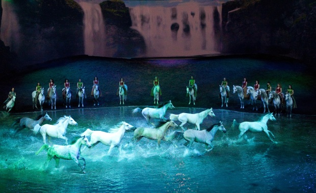 "Horses cavort in on-stage water in ""The Travelers VI"" number in Cavalia's Odysseo.  Photo Credit: François Bergeron"