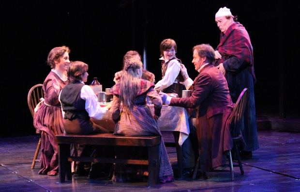 """Ebenezer Scrooge (David Coffee) watches the Cratchit family celebrate Christmas in """"A Christmas Carol"""" at North Shore Music Theatre. Photo © Paul Lyden"""