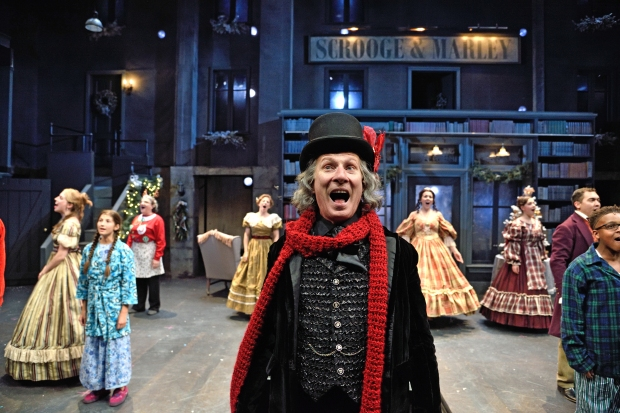 Brian McEleney as Ebenezer Scrooge with the ensemble of A Christmas Carol,directed James Dean Palmer at Trinity Rep. Set design by Michael McGarty, lighting design by Seth Reiser, costume design by Michael Krass. Photo Mark Turek.